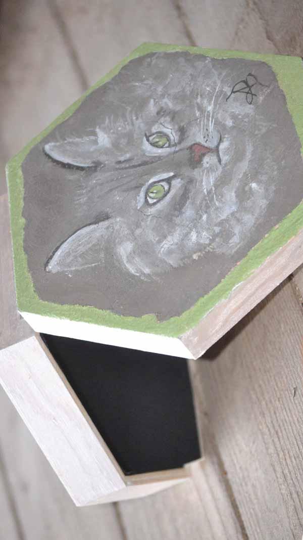 Boite à bijou hexagonale avec une fresque représentant une tête de chat sur fond noir