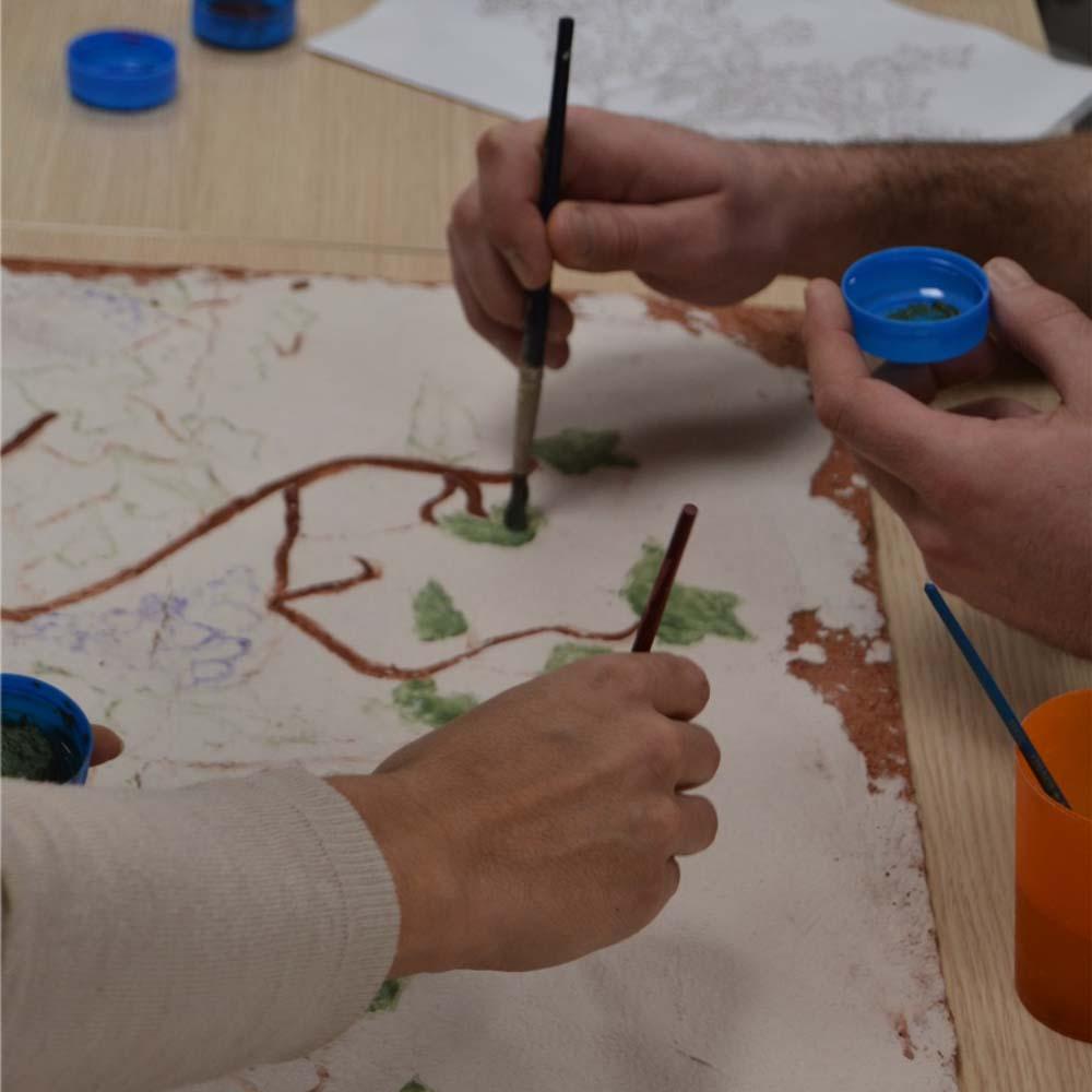 Gros plan sur deux mains peignant une fresque collective lors d'un atelier-fresque de L'Atelier Antique